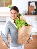 Young woman holding grocery shopping bag with vegetables . Standing in the kitchen — Stock Photo