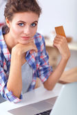 Smiling woman online shopping using computer and credit card in kitchen — Stockfoto