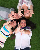 Four young women lying on green grass with hands up — Stock Photo