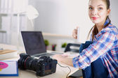 Female photographer sitting on the desk with laptop — Stock Photo