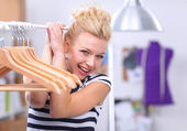 Beautiful young stylist near rack with hangers in office — Stock Photo