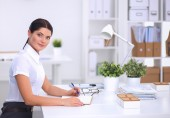 Attractive businesswoman sitting  on desk in the office — Stock Photo