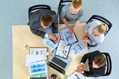 Business people sitting and discussing at business meeting, in office — Stock Photo