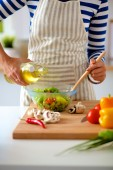 Young woman mixing fresh salad — Stock Photo