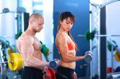 Schöne frau im fitnessstudio trainieren mit ihrem trainer — Stockfoto