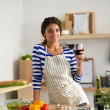 Young woman cutting vegetables in kitchen, holding a glass of wine — Stock Photo #74046137