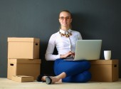 Woman sitting on the floor near a boxes  with laptop — Stock Photo