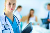 Woman doctor standing with folder at hospital — Stock Photo