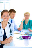 Beautiful young smiling female doctor sitting at the desk — Stock Photo