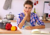 Smiling young woman in the kitchen, isolated on christmas background — 图库照片
