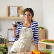 Young woman cutting vegetables in kitchen, holding a glass of wine — Stock Photo #75260769