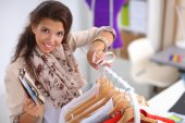 Beautiful young stylist woman near rack with hangers — Stock Photo