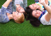 Four young women lying on green grass  — Stock Photo