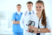 Attractive female doctor in front of medical group — Stock Photo