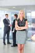 Business woman standing in foreground with a tablet in her hands — Stock Photo