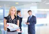 Business woman standing in foreground with a folder in her hands — Stock Photo