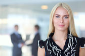 Business woman standing in foreground  in office — Stock Photo