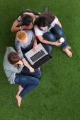 Young women lying on the grass using a laptop together — Stock Photo