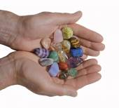 Male crystal healer offering selection of tumbled healing stones — Stock Photo