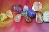 Close up of chakra gemstones on rainbow colored chiffon material — Stock Photo
