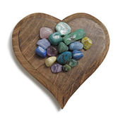 Chakra Crystal tumbled stones on wooden heart plaque — Stock Photo