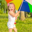 Little fun beautiful girl walks in the Park with colorful umbrella — Stock Photo #51851143