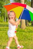 Little fun beautiful girl walks in the Park with colorful umbrella — Stock Photo