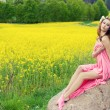 Sexy beautiful girl in pink fabric with long hair with flowers on his head sitting on the stones near the field with rape on a Sunny summer day — Stock Photo #52558415