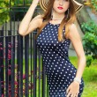 Very sexy girl with red lips in the hat dress with polka dots standing around outside in the Park on a Sunny summer day — Stock Photo #52624389