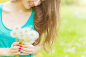 Beautiful happy smiling girl with long dandelions in the hands of shorts and a t-shirt is resting in the Park on a Sunny day — Stock Photo