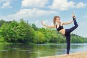 Beautiful young girl is engaged in sports, yoga, fitness on the beach by the river on a Sunny summer day — Zdjęcie stockowe