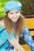 Beautiful smiling girl in a blue hat with pink headphones sitting in the Park on a bench and listening to music — Stock Photo