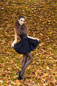 Beautiful young girl on the background of the leaves in autumn day on the street with fantasy makeup in a black dress with big sexy lips — Stock Photo