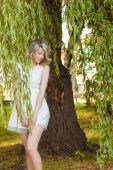 Portrait of a beautiful sexy girl with big full lips, with white hair in a white dress near a tree — Stock Photo