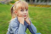 Little beautiful girl with tails sitting on the grass in the Park — Stock Photo