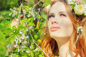 Beautiful sexy girl with red hair with flowers in her hair stands near a blossoming Apple trees — Stock Photo