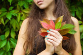 Fallen autumn leaves in the hands of a beautiful girl with full lips — Stock Photo