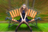 Beautiful young girl autumn day on the street with fantasy makeup in a black dress with big sexy lips sitting on a bench in the Park — Stock Photo