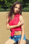 Сексуальная красивая девочка с длинными темными волосами, сидящими в шортах из денима на пляже в солнечный день — Стоковое фото