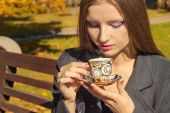 Beautiful woman with a Cup of tea in the beautiful makeup sitting in the Park on a bench and drink hot tea in the autumn Sunny day — Stock Photo