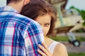 красивая счастливая влюбленная пара, стоящая около старых самолетов, обнимая девочку, просматривает плечо парня — Стоковое фото