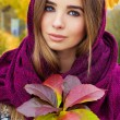 Beautiful charming young attractive girl with large blue eyes with a handkerchief on his head, long dark hair holding a fall bouquet of leaves on a cold autumn day — Stock Photo #56372987