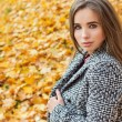 Beautiful charming young attractive girl with large blue eyes, with long dark hair in the autumn forest in coat — Stock Photo #56459069