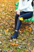 Beautiful legs girl in black pants and boots with yellow leaves in the hands of sitting on the bench in autumn Park — Stock Photo