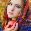 Beautiful young sweet girl in a headscarf with the rim on the head with a red Apple in his hand, like a fairy tale character with blue eyes — Stock Photo #57396747