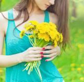 庭を歩晴れた夏の日の美しい少女と手の中に黄色のタンポポを保持 — ストック写真