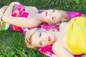 Beautiful sexy girls, sisters with bright makeup and red lips lie on a bright blanket in a Park on a warm summer day — Stock Photo