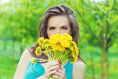 Beautiful girl in a Sunny summer day walking in the garden and keeps yellow dandelions in the hands — Stock Photo