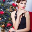 Beautiful sexy happy smiling young woman in evening dress with bright makeup with red lipstick sitting near the Christmas tree in a festive Christmas evening — Stock Photo #60460063