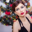 Beautiful sexy happy smiling young woman in evening dress with bright makeup with red lipstick sitting near the Christmas tree in a festive Christmas evening — Stock Photo #60544421